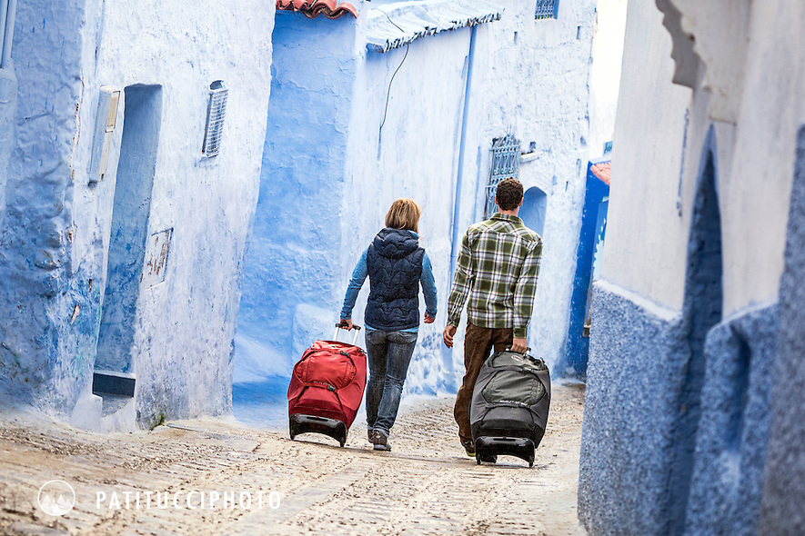 Travelers with their luggage walking through Chefchaouen, known as the Blue City, Morocco