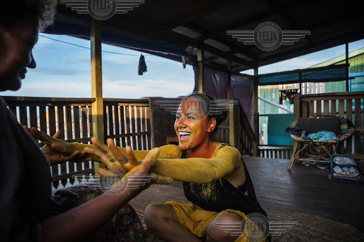 Ella Keahi, 55, helps her 18 year old niece Jessica to put on 'hala'ei', a turmeric paint that women and girls from Ontong Java Atoll apply when they participate in cultural shows, traditional celebrations and weddings. Lord Howe Settlement, a district of the capital Honaria, is populated by people from Ontong Java Atoll (AKA Lord Howe Atoll), a Polynesian outlier of the Solomon Islands. Its people have been moving to Lord Howe Settlement in search of a better life since the 1970s. Climate change leading to rising sea levels and consequent food insecurity now means the atoll is existentially threatened. The remaining Ontong Javanese people are considering the possibility of complete relocation to Santa Isabel Island and to Honiara. However, with Lord Howe Settlement itself suffering the consequences of extreme weather and overcrowding, community leaders believe it is not a viable long term home. Furthermore, they fear that the Ontong Javanese people's Polynesian identity will be lost as a new generation is brought up in a location with no connection to ancestral land. Their identity will be weakened as they become a minority amongst Melanesian communities that have vastly different traditions and speak different languages.