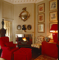 A small odd-shaped sitting room with fireplace and predominantly red-upholstered furniture