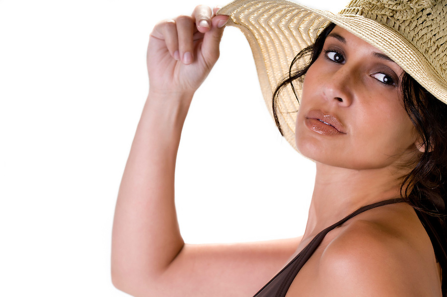 Portrait of hispanic woman wearing beach hat, looking at camera.