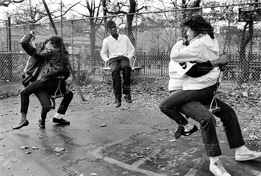 USA. New York City. Lower East Side. Tomskins Park. Teenagers on a swing. Two couples are hugging and kissing while a Afro-American boy is left alone. African Americans, also referred to as Black Americans or Afro-Americans, are citizens or residents of the United States. © 1985 Didier Ruef