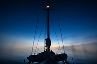 Sihouette of sailboat mast while drifting in summer twilight off the east coast of Greenland