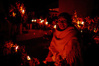 Candles light a woman keeping vigil by a grave as Day of the Dead celebrations begin in this town outside of Oaxaca city. Dia de los Muertos is Mexico's most characteristic fiesta when the souls of the dead return to the earth and families build alters in their homes and visit the cemeteries. They commune with their loved ones by taking gifts of flowers and the favorite foods of the deceased. A happy atmosphere of celebration complete with music and families spending the night in the cemetery lighting candles, burning incense and staying through the night.