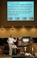 STAFF PHOTO BEN GOFF  @NWABenGoff -- 06/29/14 The Rev. Carness Vaughan speaks during his Summer at the Movies sermon at Central United Methodist Church in Rogers on Sunday June 29, 2014. Vaughan interspersed showing clips form the movies 'Up,' 'The Sandlot' and 'The Blind Side' on the screen, top, with his sermon on the theme 'answering the call.'