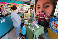 Occidental College UEPI CA Farm to School Program Manager Yelena Zeltser talks to local residents and hands out bags of avocados and taste samples in Mother's Nutritional Center in the Highland Park neighborhood of Los Angeles. The program is intended to promote locally grown fruits and vegetables. (Photo by Marc Campos, Occidental College Photographer)