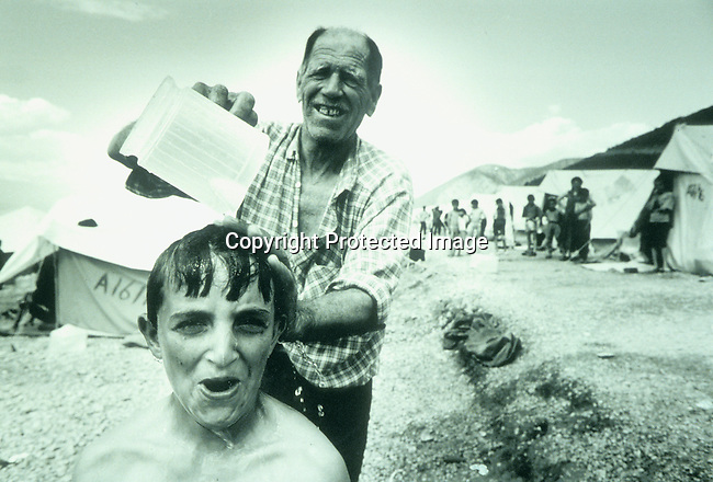A refugee boy gets a shower from his grandfather on April 21, 1999 in refugee camp in Cegrane, Macedonia. Hundreds of thousands of people fled Serb terror into Albania and Macedonia in early 1999 and stayed for months in camps..©Per-Anders Pettersson/iAfrika Photos