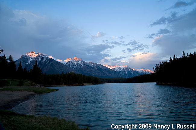 Johnson Lake in Banff National Park with the sun touching the tops of the mountains duirng sunset