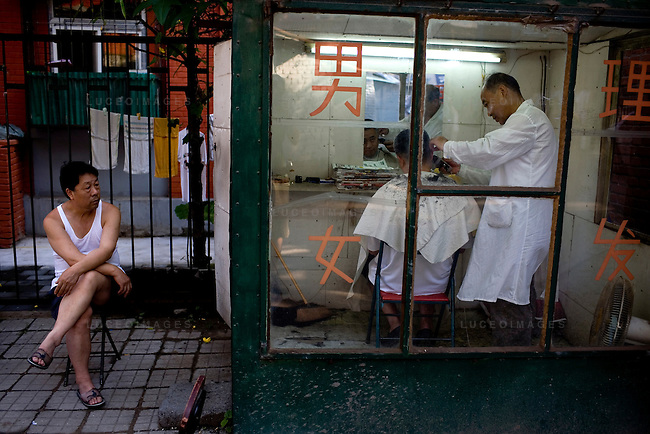 A local man gets his haircut at a small barber shop in Beijing, China on Friday, August 22, 2008.  The haircut cost less than $0.50 USD. Kevin German