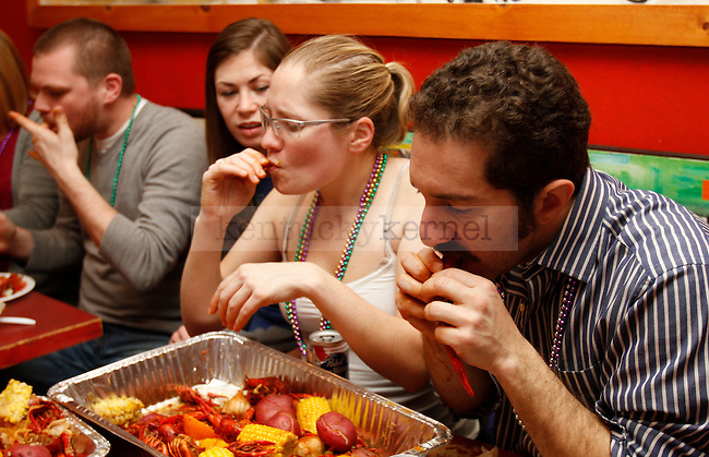 Engineering junior Diego Rich and UK graduate Trish Murphy eat during the Mardi Gras celebration at Bourbon and Toulouse in Lexington, Ky., on Tuesday, February 12, 2013. Photo by Genevieve Adams | Staff