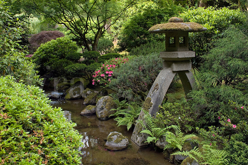 A stone lantern above a creek at the Portland Japanese garden, considered the most authentic outside of Japan - PORTLAND, OREGON.