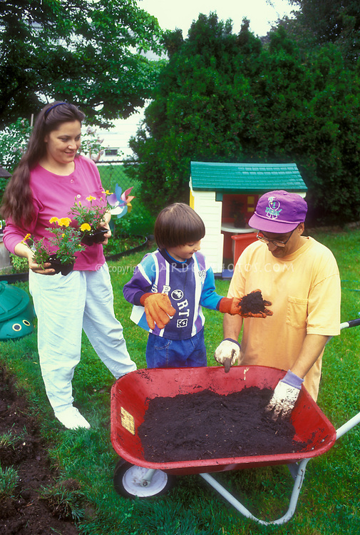 Mother, father, son, gardening in backyard with red wheelbarrow of soil, big gloves on child, intergenerational family enjoying nature and garden
