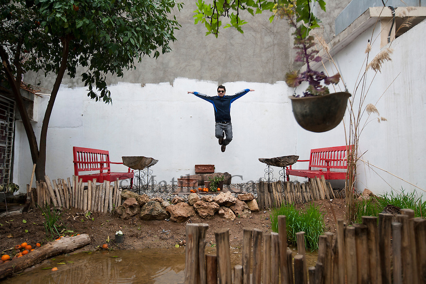 Iraq - Kurdistan - Sulaymaniyah -   Jamal Penjweny flying in the courtyard of his Cafe' 11 recently open in the city center