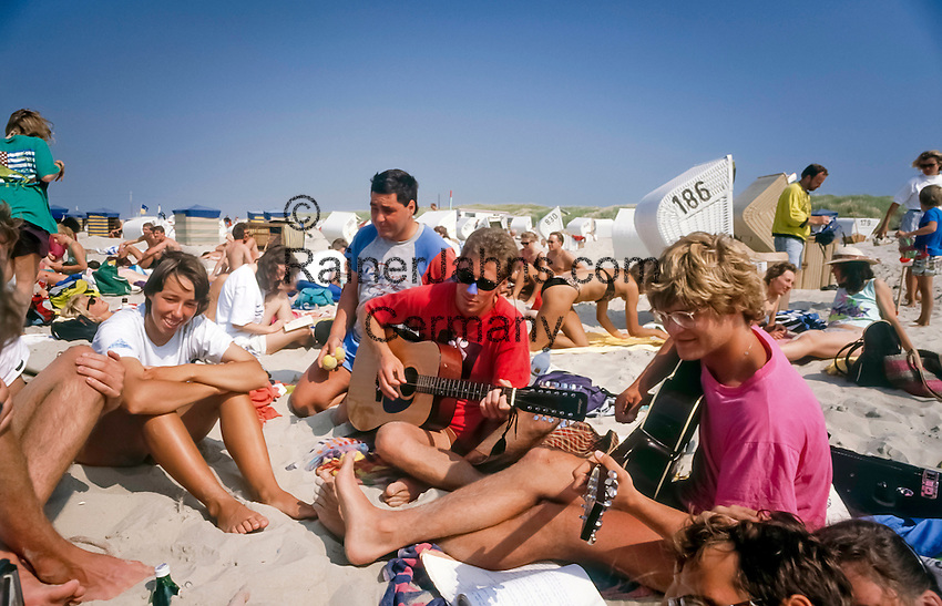 Germany, Lower Saxony, East Frisian Island, Baltrum: Teenager enjoying holidays on the beach, playing guitar and singing together | Deutschland, Niedersachsen, Ostfriesische Insel, Baltrum: Jugendliche geniessen die Ferienzeit am Strand, musizieren und singen gemeinsam