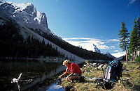 CANADA, ALBERTA, KANANASKIS, MAY 2002. A camper fills he rwater bottle at Elbow Lake.  The Kananaskis Country provincial park is home to Canada's most beautiful nature and wildlife. It has also escaped the mass tourism as in Banff National Park. Photo by Frits Meyst/Adventure4ever.com