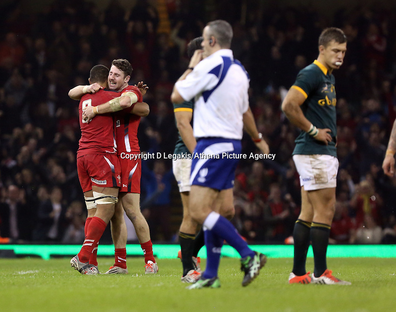 Pictured L-R: Taulupe Faletau of Wales hugs team mate Alex Cuthbert as the referee marks the end of the game with the final whistle, a South Africa player stand dejected (R) Saturday 29 November 2014<br /> Re: Dove Men Series 2014 rugby, Wales v South Africa at the Millennium Stadium, Cardiff, south Wales, UK.