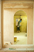 Plastering student finishes off his work using a trowel and a water spray, Able Skills, Dartford, Kent.