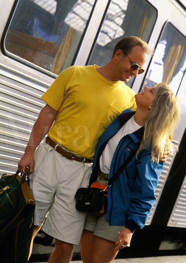 A smiling young couple embraces outside of a train.
