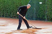 August 24, 2014, Netherlands, Amstelveen, De Kegel, National Veterans Championships, Preparing the clay courts after rainfall<br /> Photo: Tennisimages/Henk Koster