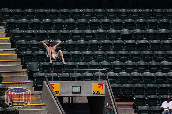 OAKLAND, CA - SEPTEMBER 7:  A shirtless fan of the Oakland Athletics sits in an empty section of seats during the game against the Kansas City Royals at O.co Coliseum on September 7, 2011 in Oakland, California. Photo by Brad Mangin
