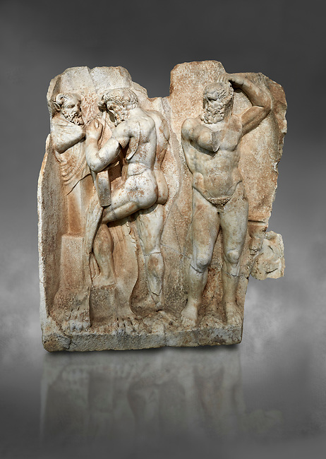 Roman Sebasteion relief sculpture of  Herakles is preparing to wrestle the Libyan giant Antaios. Aphrodisias Museum, Aphrodisias, Turkey. Against a grey background.<br /> <br /> Herakles (left) is taking off his bow case to hang it on a pillar statue. Antaios (right) is binding up his head with ear protectors, next to him stands an oil basin used in the palaistra (wrestling ground). Antaios was a famous wrestler who challenged and killed all visitors to his country, until he was defeated by Herakles.