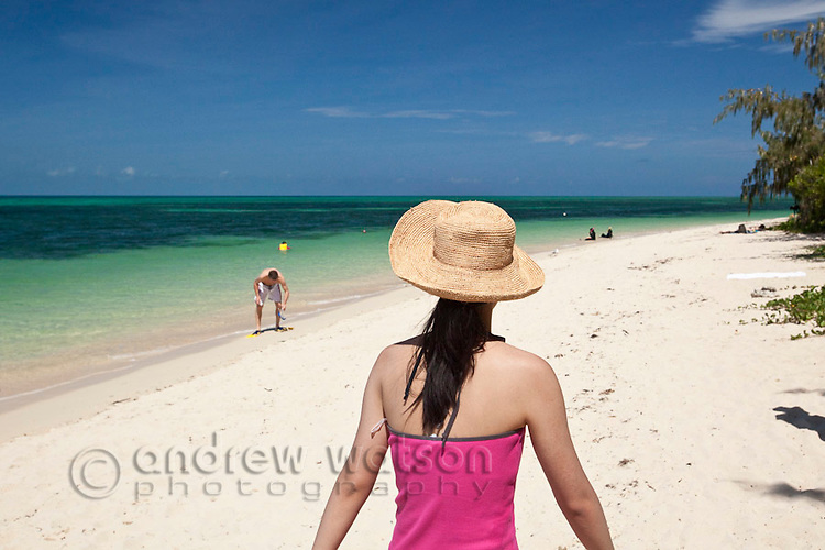 Woman walking along beach on Green Island - a coral cay off the coast of Cairns.  Great Barrier Reef, Queensland, Australia
