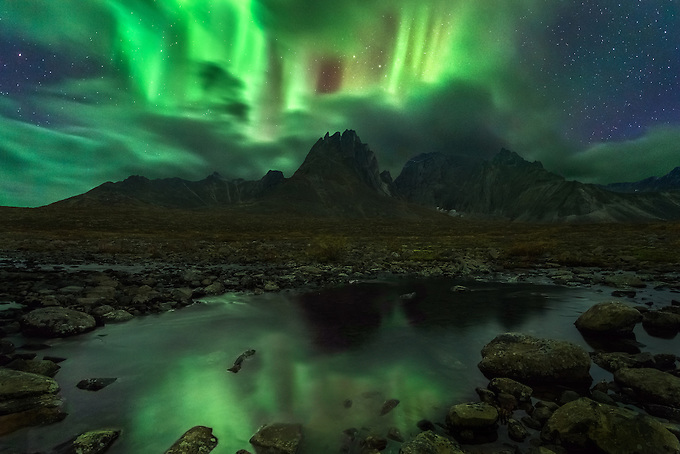 The aurora bursts through the clouds in the night sky reflected in a small tributary below, deep in the wilderness of the Ogilvie Mountains, Yukon Territory.