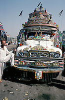 The driver of a typically colourful bus parked in the bus station at Rawalpindi in Pakistan poses proudly in front of it.