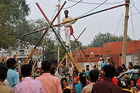 Kishan Bharti works as a tall man and rope artist and stays at Katputly colony in New Delhi, India. 16.11.2009. Kathputly colony is a slum area in West Delhi. This slum seems like any other slum areas of modern India with dysfunctional electricity, non existing sanitation and poverty. As a part of Delhi, this is also ailed with water crisis. Large families live their lives crammed together in a single room with all the odds which complement poverty. One thing which differentiates this slum with any other is the people living in the colony. Nearly everybody in this slum is a traditional performing artist; and they have been migrating to this area for last 50 years from different parts of the country for a better livelihood. They are magicians, acrobats, jugglers, puppeteers, dancers and musicians. These artistes perform in star rated hotels, marriage ceremonies of the richer section, functions, and festivities all around the country and the world. Most of the artisans I met here, have performed in Europe and America but such opportunities are rare to come by. They struggle to keep their art form alive. They say that they don't get any help or support from the government for their basic needs and for the well being of the Kathputly colony -  though they have uphold the prestige of the country internationally. Polluted air, dirty alleys smelling of urine, colourful dress and sound of music characterise Kathputly colony, which is the one of its kind in India. Arindam Mukherjee