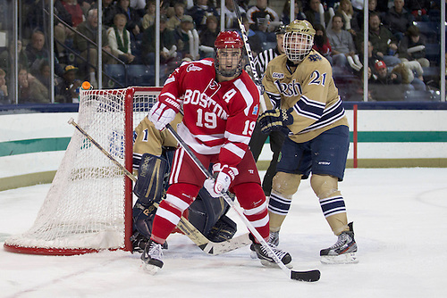 Notre Dame right wing Bryan Rust (#21) defends Boston University forward Justin Courtnall (#19) in third period action of NCAA hockey game between Notre Dame and Boston University.  The Notre Dame Fighting Irish defeated the Boston University Terriers 5-2 in game at the Compton Family Ice Arena in South Bend, Indiana.