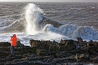 WEATHER PICTURE WALES<br /> Pictured: A man stands on the rocks to  watch the waves as they crash against the promenade wall and the lighthouse in the seaside town of Porthcawl, south Wales, UK. Wednesday 03 January 2018<br /> Re: Storm Eleanor affects parts of the UK.