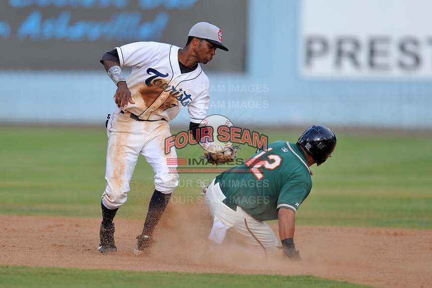 Asheville Tourists shortstop Rosell Herrera #7 applies the tag as Jesus Solorzano #12 slides in safely during game one of a double header against the Greensboro Grasshoppers on July 2, 2013 in Asheville, North Carolina.  The Tourists won the game 5-3. (Tony Farlow/Four Seam Images)