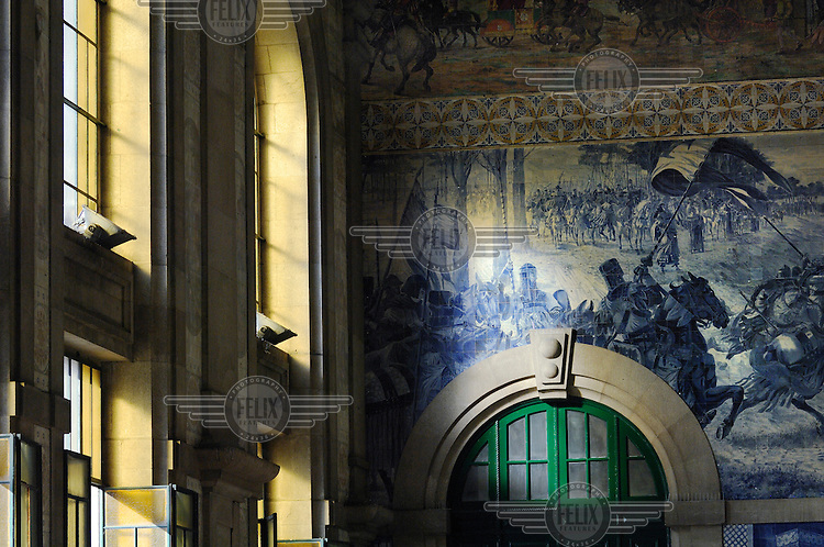 View of blue azulejos (Portuguese tiles) decorating the main hall of the Sao Bento Train Station in Porto's city centre, illustrating scenes from Portuguese history in a romantic style.