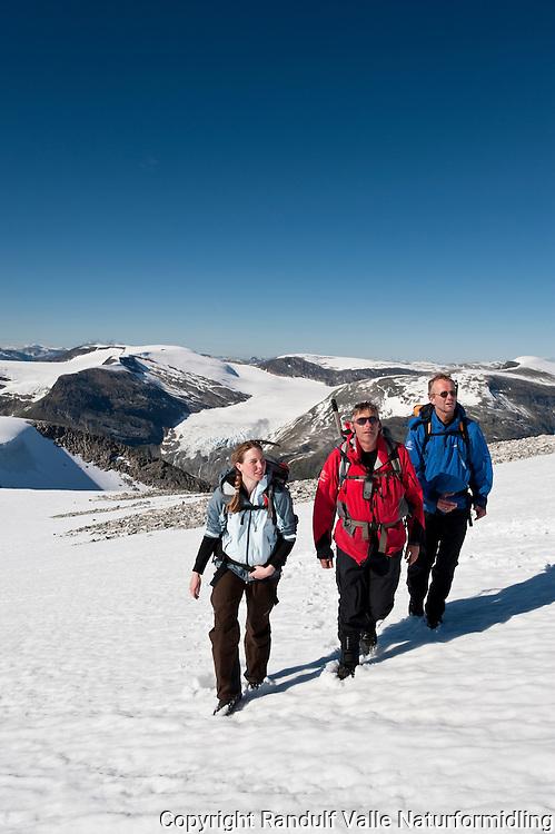 Tre personer på snøfelt på Bødalsfjellet. Breen Skålbreen i bakgrunnen. ----- Hikers on the mountain Bødalsfjellet.