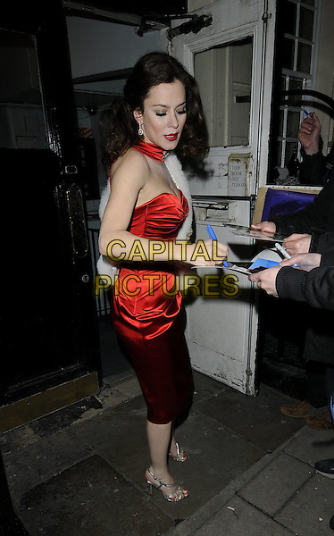 "ANNA FRIEL.leaving after her evening performance in ""Breakfast At Tiffany's"", Theatre Royal Haymarket, London, England, UK,.December 3rd 2009..full length red silk satin strapless neck collar dress signing autographs fans silver strappy sandals .CAP/CAN.©Can Nguyen/Capital Pictures"