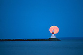 Full moonrise behind the upper harbor breakwall lighthouse in Marquette, Michigan, Lake Superior.