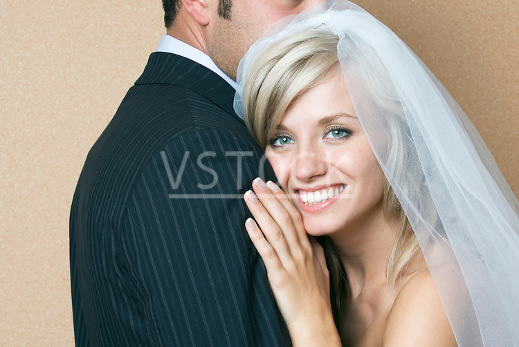 Bride and groom embracing, portrait