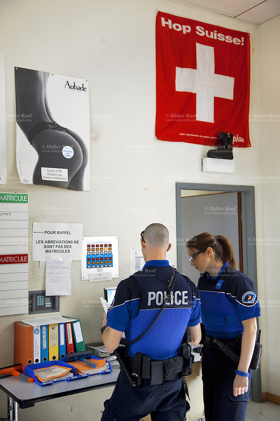 Switzerland. Geneva. Paquis police station. Two police officers check on a computer the identities of men who haver been earlier arrested. A swiss flag and a poster for Aubade lingerie ( a beautiful naked woman with a sexy underwear ) are on the wall. A policeman's shoe is placed on a lamp above the door. A police station or station house is a building which serves police officers and contains offices, locker rooms, temporary holding cells and interview/interrogation rooms. Both policemen are wearing a ballistic vest, bulletproof vest or bullet-resistant vest which is an item of personal armor that helps absorb the impact from knives, firearm-fired projectiles and shrapnel from explosions, and is worn on the torso. Soft vests are made from many layers of woven or laminated fibers and can be capable of protecting the wearer from small-caliber handgun and shotgun projectiles, and small fragments from explosives such as hand grenades. The flag of Switzerland consists of a red flag with a white cross (a bold, equilateral cross) in the centre. It is a sovereign-state flag. 15.05.12 © 2012 Didier Ruef