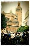 Group of tourists by the Giralda Tower and the Cathedral, Seville, Spain. Taken with tilted lens to get shallower depth of field and digitally edited to look like an old print.