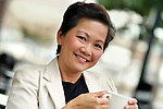 Smiling Asian woman with cup of coffee