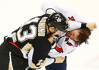 Nick Bonino #13 of the Pittsburgh Penguins fights Taylor Chorney #4 of the Washington Capitals in the second period during the game at Consol Energy Center in Pittsburgh, Pennsylvania on December 14, 2015. (Photo by Jared Wickerham / DKPS)
