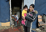 Ivana Ibraimovic holds her 8-month old son Rasim while her 10-year old son Brandon comes out of their house in a Roma settlement in Belgrade, Serbia. The families that live here, many of whom survive from recycling cardboard and other materials, are under constant threat of eviction in order to make way for new high-rise office buildings. Note: residents of this settlement were forcibly evicted in April 2012, two months after this photo. Many were relocated in metal shipping containers at the edge of the city.