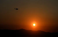 Pictured: A fire helicopter is seen flying at dawn.<br /> Re: A forest fire has been raging in the area of Kalamos, 20 miles north-east of Athens in Greece. There have been power cuts, country houses burned and children camps evacuated from the area.
