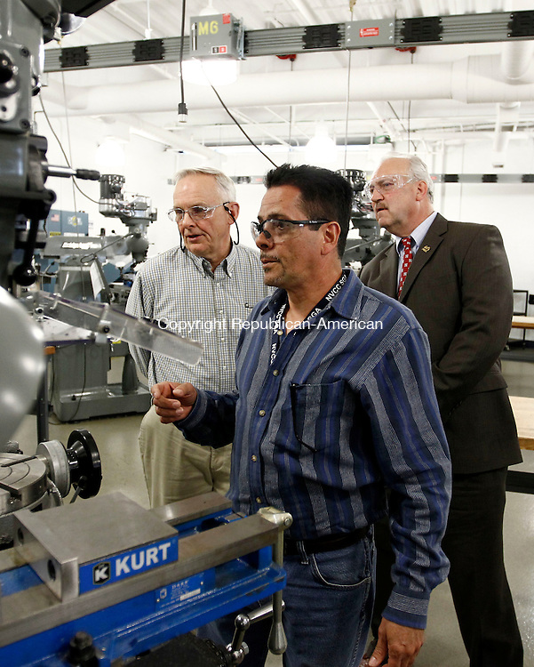Waterbury, CT- 24 April 2014-042414CM02- Naugatuck Valley Community College manufacturing student, Armando Rodriguez of Waterbury, gives a demonstration on a Bridgeport Vertical Milling machine at the college in Waterbury on Thursday.  Looking on is Ed Tremblay, treasurer with the local Precision Metalforming Association, left, and Bill Adler chairman of the Board of Directors of The Precision Metalforming Association .  The college's Advanced Manufacturing Program received a grant from the Precision Manufacturing Association Educational Foundation.  The grant will help recruit future students into the program.    Christopher Massa Republican-American