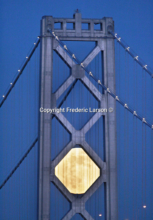The full moon took on a different shape as it pass behind the south tower of the Bay Bridge Thursday night during the twilight hours from the Embaradero, San Francisco, California..