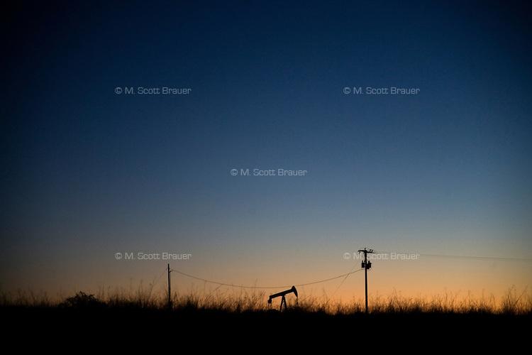 An oil pump is silhoutted against the dawn sky near Sumatra, Montana, USA.