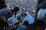 "Teenage tourists from Colombia lay down on the newly opened glass balconies ""The Ledge"" at the Skydeck at the Sears Tower in Chicago, Illinois on July 6, 2009."