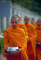 Buddhist monks make their rounds each morning to collect donations of food from the faithful, Chaing Mai, Thailand