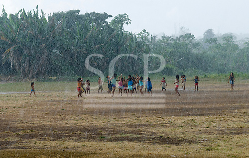 Pará State, Brazil. Aldeia Apyterewa (Parakana). Children playing ball in the rain.