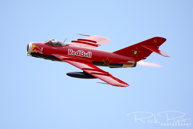 "Bill Reesman demonstrates his meticulously maintained Red Bull MiG-17F during an air show at Madera, California, in May of 2009. Reesman's MiG-17F was built in Poland in 1959 and entered active service in the Polish Air Force as a Cold War warrior, patrolling the Iron Curtain for about 25 years until it was parked in an aircraft ""bone yard"" in Poland. Reesman had the aircraft rebuilt after his first MiG 17 exploded and caught fire during takeoff."