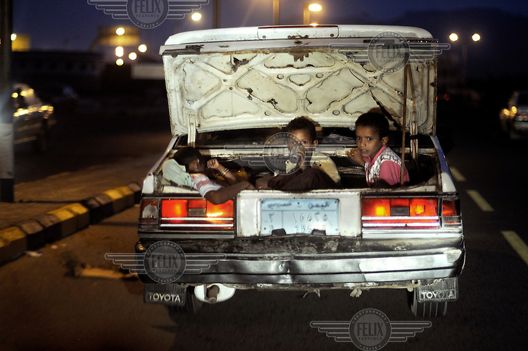 Three children ride in the open boot of a car as it drives through the port city.